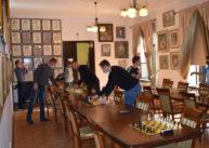 Przygotowania doturnieju szachowego. Zawodnicy ustawiają figury szachowe naplanszy.