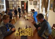 W sali ustawione są dwa rzędy stołów. Przy nich zawodnicy siedzą igrają wszachy. Jeden zuczestników stoi przy stole.