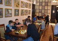 Zbliżenie najeden stół. Napierwszym planie dwóch uczestników rozgrywa partię szachów. Obok jeden zzawodników przygląda się grze. Wtle widoczni pozostali gracze.