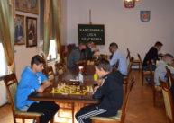 Zbliżenie najeden stół. Napierwszym planie dwóch uczestników rozgrywa partię szachów. Wtle widoczni pozostali gracze.