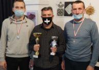 Na zdjęciu stoi trzech mężczyzn. Jeden trzyma dwa puchary, adwóch ma zawieszone naszyi medale.