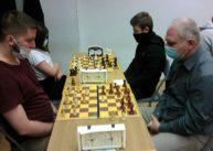 Przy zestawionych zesobą stołach siedzą szachiści.